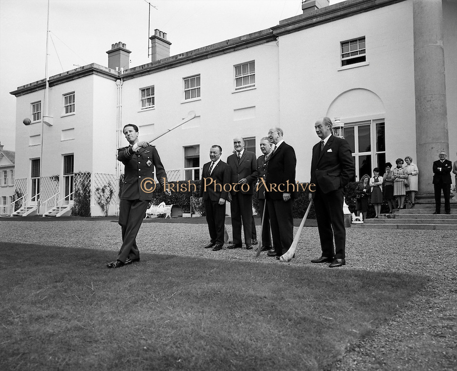 Having had a few lessons from All-Ireland winner Jack Lynch, King Baudouin takes a puck at the sliotar in the grounds of the Aras. Watching on are (l to r)Sean O Siochain, GAA President, Minister Frank Aiken, Presiden Eamon de Valera, and An Taoiseach Jack Lynch..17.05.1968