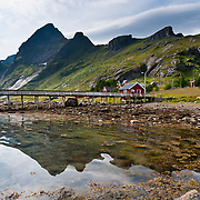 Sharp mountains at Vindstad on Moskenesøya (Moskenes Island) rise above Reinefjord in the Lofoten archipelago, Nordland county, Norway, Europe. Panorama stitched from 2 overlapping photos.