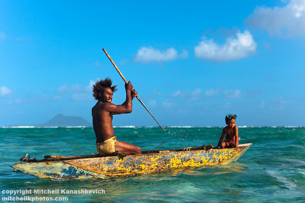 Ni Vanuatu father and son going out to sea in a traditional outrigger canoe. Rah Lava Island, Torba Province, Vanuatu