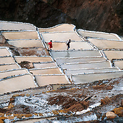 "Since pre-Inca times, salt farmers at the saltworks (salinas) near Maras have evaporated salty water from a subterranean stream in Peru, South America. A rough dirt road connects Maras (in the Urubamba/Vilcanota River Valley, Sacred Valley of the Incas) with Cuzco (40 km north) and other towns. The cooperative system of pond farmers was established during the time of the Incas, if not earlier, and is traditionally available to any person wishing to harvest salt. Intricate channels redirect water flow through several hundred ancient terraced ponds. As water evaporates from the sun-warmed ponds, it becomes supersaturated and salt precipitates as crystals. A pond keeper closes the water-feeder notch, allows the pond to go dry, then scrapes and carries away the dry salt. Salt color varies from white to a light reddish or brownish tan, depending on ""farmer"" skills. Cropped from a 35mm film slide, 2003. Published in ""Light Travel: Photography on the Go"" book by Tom Dempsey 2009, 2010."