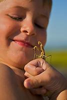 A close-up of a boy with a praying mantis.