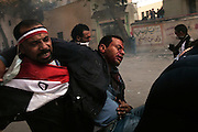 A wounded Egyptian protester bloodied during clashes with security forces is taken to a field hospital during demonstrations November 22, 2011 near Tahrir square in central Cairo, Egypt. Thousands of protestors demanding the military cede power to a civilian government authority clashed with Egyptian security forces for a fourth straight day in Cairo, with hundreds injured and at least 29 protestors killed.  (Photo by Scott Nelson)