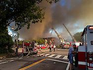 Firemen struggle to control the blaze.