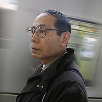 MITSURU KONO, victim of the 1995 Tokyo underground sarin gas attack by Aum Shinrikyo Supreme Truth Cult, standing on his local train platform, in Tokyo, Japan
