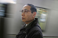 MITSURU KONO, victim of the 1995 Tokyo underground sarin gas attack by Aum Shinrikyo Supreme Truth Cult, standing on his local train platform, in Tokyo, Japan
