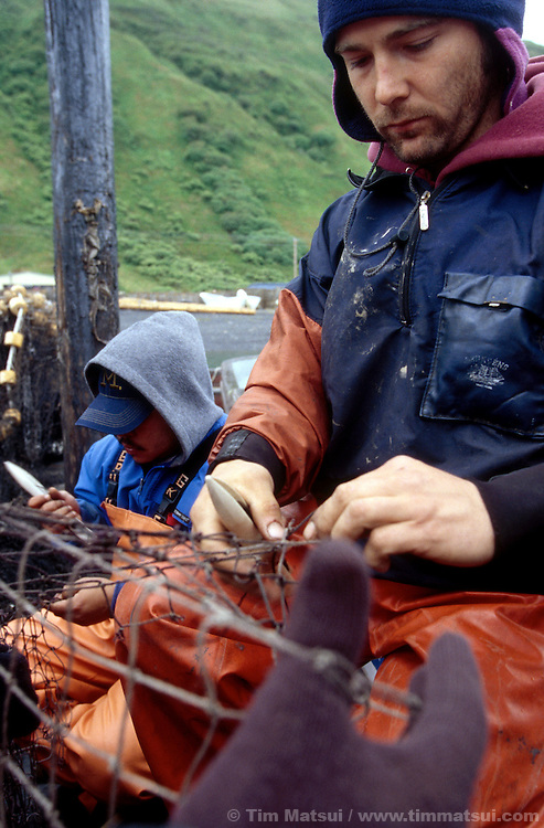 Repairing gill nets for salmon fishing in Old Harbor, Kodiak Island, Alaska.