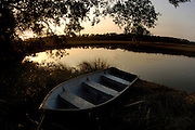 A small wooden row-boat on the bank of a creek near a salt-water marsh near the Geechee-Gullah community of Hog Hammock on Sapelo Island. Property owners are facing higher taxes, and fees from the county tax collector threatening an already fragile community of Hog Hammock. (Stephen Morton for The New York Times)