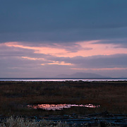 A cloudy winter sunrise colors the sky over Boundary Bay, located near the United States/Canadian border in British Columbia, Canada. The San Juan Islands of Washington state are visible in the background.