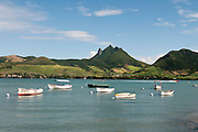 Boats at a bay on the South East coast with mountains and sugar cane fields in the distance.