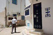A Tunisian man  holding loaves of bread as he passes by the home of a Jewish family decorated with the symbol of menorahs in the Hara Kebira neighborhood located on  the Tunisian island of Djerba on May 25,2016.  Five years after Tunisia's revolution, and a year after three deadly ISIS attacks, the 1,100 Jews in this tiny island community of Djerba say they do not feel threatened living in Tunisia.(Photo by Heidi Levine).