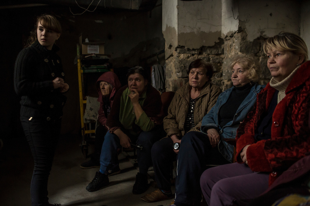 DONETSK, UKRAINE - JANUARY 29, 2015: Local residents sit in the dark during a power outage in an underground bomb shelter in the Petrovskyi district of Donetsk, Ukraine. The neighborhood has been shelled heavily in the past few days, forcing many people back to the shelters they first fled to in the summer. CREDIT: Brendan Hoffman for The New York Times