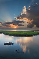A beacon of light announces the rise of the sun and illuminates the green marsh lands of the South Carolina coast. North Charleston, SC