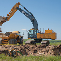 John Deere excavator on dumping dirt on wind project site