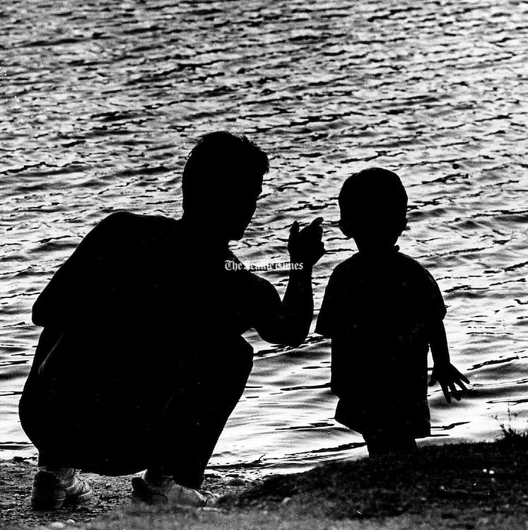 And watch the ripples: A father teaches his son, 2, the finer points of skipping stones at Five-Mile Lake Park in Federal Way. (Mike Levy / The Seattle Times, 1988)