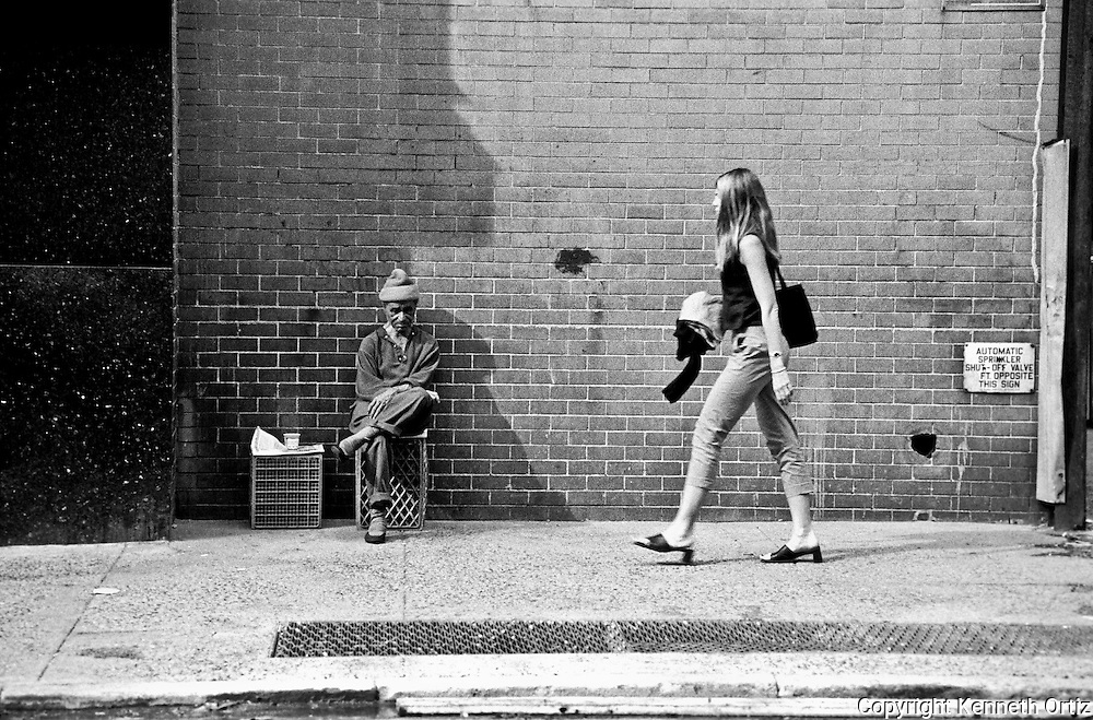 A man sitting on an egg crate while a young woman walks by.