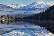 Fog forms ribbons in the horizon between forest and Mendenhall Glacier as the glacier casts its reflection on a sunny, blue sky day in Auke Lake, Alaska.