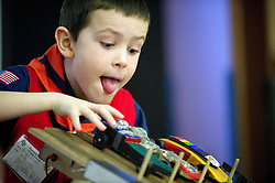 Pack 67 Cub Scout Brian Green, 7, concentrates as he places his Pinewood Derby car on the track at Davey Jackson Elementary School on Saturday.
