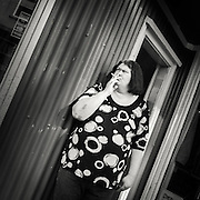 Woman standing out side a shop in down town Reykjavik smoking a cigarette