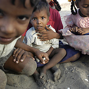Children sit on the beach in the fishing village of Perumalpettai in Tamil Nadu, India on January 17, 2005, after the area was struck by the Indian Ocean Tsunami on December 26, 2004, killing 37 of the villagers and destroying nearly all of their fishing boats. Generated by an earthquake on the ocean floor, the tsunami devastated the fishing industry along the southeastern coast of India.