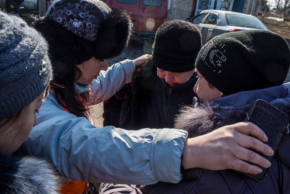 MARIINKA, UKRAINE - FEBRUARY 20, 2016:  Lyuba Shpihernyuk, second from left, a volunteer with the Christian Help Center of the Church of the Transfiguration, a prays with local residents in Mariinka, Ukraine. The Donetsk suburb has been the scene of some of the heaviest fighting recently between Ukrainian forces and pro-Russian rebels. CREDIT: Brendan Hoffman for The New York Times