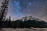 The stars of Taurus, including the Pleiades, rising above Mount Kerkeslin, with Capella and Auriga at top left. Castor and Pollux in Gemini are among the trees at lower left. The winter Milky Way runs from Capella down to Gemini. <br /> <br /> This is from the Athabasca Falls area, looking east over the river flats. High cloud added the natural star glows but also some sky discolouration. The rising Moon off frame is beginning to light the sky. <br /> <br /> This is a stack of 6 exposures for the ground, mean combined to smooth noise, and one exposure for the sky, all 25 seconds at f/2 with the Sigma 20mm lens and Nikon D750 at ISO 6400. Taken October 22/23, 2016.