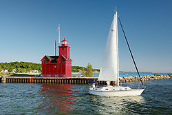 A sailboat heads past Big Red to view the Lake Michigan sunset.<br /> Holland, Michigan