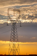 Power lines and transmission towers silhouetted against the rising sun, Columbia River valley Washington USA