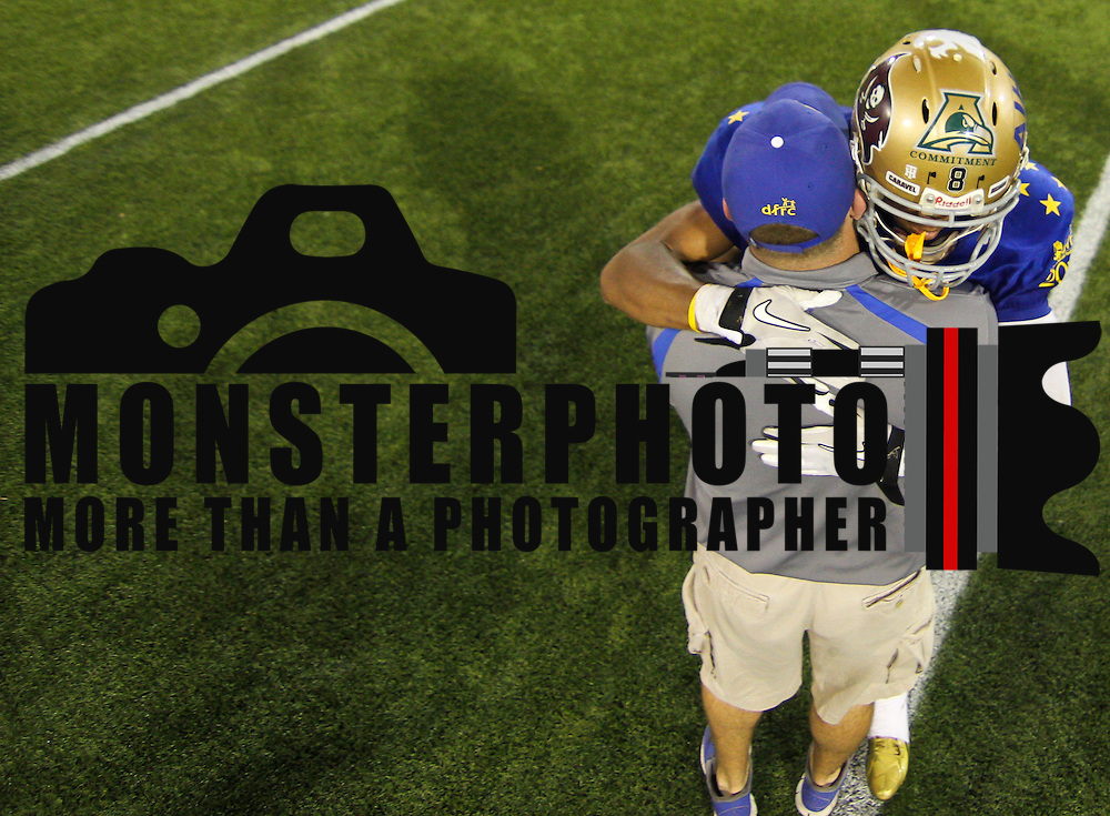 Blue cornerback Andre Patton (8) of Saint Elizabeth High School hugs his Assistant Coach David Willard after the final play of the 58th Annual DFRC Blue-Gold All-Star Football game Saturday, June. 22, 2013, at Delaware Stadium in Newark DE.