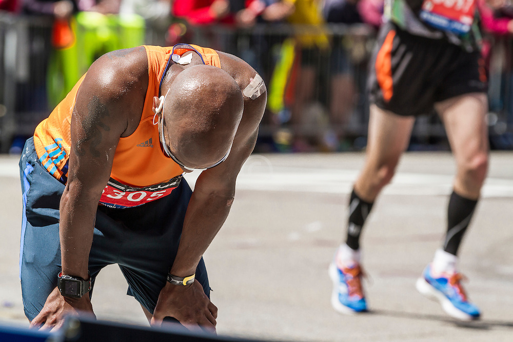 2014 Boston Marathon: exhausted runner stops on course before heading for the finish line