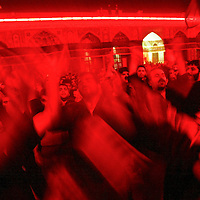 Shiite Muslim men pray inside of the Imam Hussein holy shrine at night in Karbala, Iraq. The red light in the shrine represents the blood of Imam Hussein. For the first time on Tuesday March 2, Shiite Muslims in Iraq will be able to gather at the Shiite holy city of Karbala to mark the Ashoura mourning the death of one of their most important saints, Imam Hussein. March 2004.