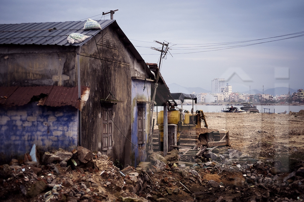 A bulldozer is parked close to a rudimentary house. Danang, Vietnam, Asia