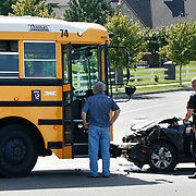 """Dillon Lane of Kennewick, right, talks with Kennewick police after colliding with a school bus in his 2001 Hyundai Elantra on Columbia Center Boulevard at 4th Avenue in Kennewick. Around 40 kids were on board from Desert Hills Middle School and Kamiakin High School. No one was hurt, """"just sore from the seatbelt kicking my ass,"""" said Lane. Kennewick police Sgt. Ken Lattin said the bus driver was at fault since she was turning left, and she would be cited for failure to yield. Another school bus came to pick up kids who hadn't already called their parents and the this bus was able to drive away. """"School buses are built to take a hit like this,"""" said Ethan Schwebke, transportation manager for Kennewick School District. """"The only thing they lose against is a semi or a train."""""""