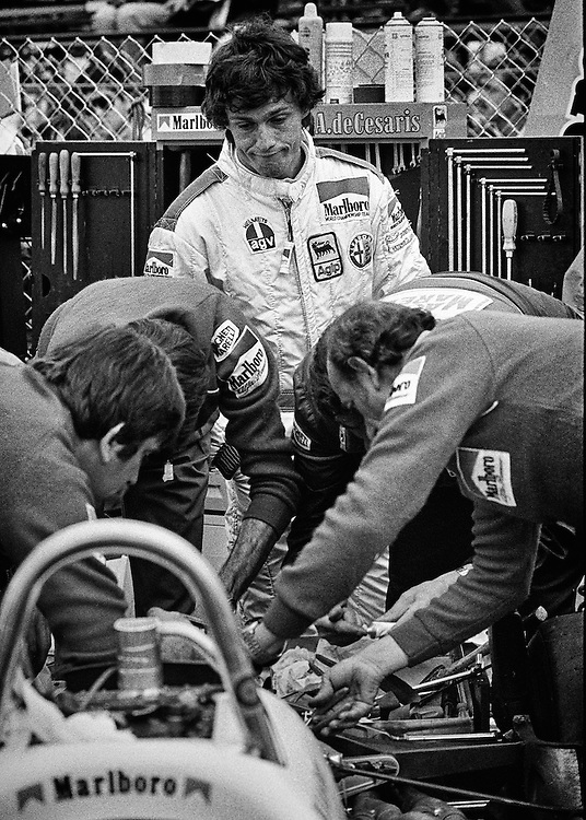 Andrea deCesaris can only grimace as Marlboro Alfa Romeo race mechanics rush to solve a transmission malfunction within minutes of the start of the 1982 Detroit Grand Prix. <br /> <br /> The Italian F1 driver had qualified the car in second and the team was frantically rushing to get the car to the grid. They would succeed. <br /> <br /> A former World Karting Champion, deCesaris would drive for McLaren, Ligier, Minardi, Brabham, Tyrrell, Jordon, Sauber as well as Alfa Romeo in over 208 races during his F1 career without ever having a victory. <br /> <br /> Here in Detroit, his transmission would ultimately fail on lap 2.