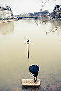 A girl with an umbrella smokes a cigarette on a bench surrounded by the water of the Seine River, in front of a drowned streetlight, Paris, 2010.