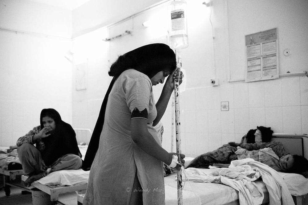 A young woman holds her iv stand, coping with the labour pain. Karachi, Pakistan, 2010