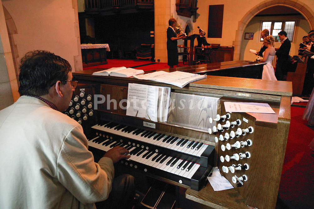 Church organist playing organ during wedding ceremony,