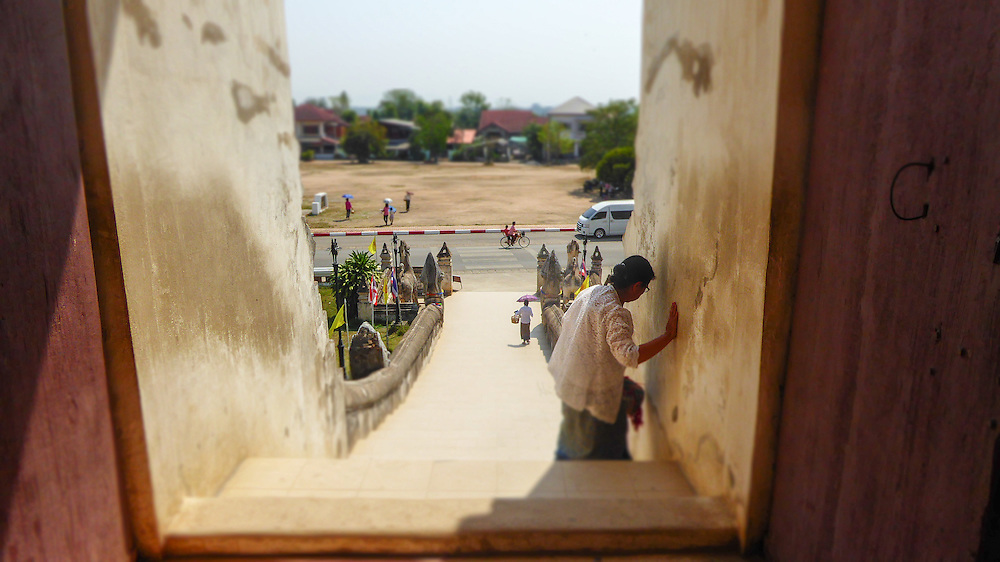 This image was taken by Nukul at Lampan Luang Temple in Thailand. In this image an older woman can be seen using the wall for support as she walks down the stairs of a temple. Nukul recalls going to such temples when she was younger, noting that mostly older people are in attendance at Temples, as opposed to younger children and teenagers. Nukul wonders why this is the case and she recognizes that the woman pictured seems so very tired, but that does not stop her from coming to pray. The woman is strong for this reason.<br /> <br /> Nukul is Thai Karen and works with the program Daughters Rising in Thailand. She has one young son who often stays in her village while she works. Nukul loves photography and recently took an interest in photographing events.<br /> <br /> &ldquo;I want to have a good job. I want to work for my family to be happy. I want to travel everywhere and go many many countries, like Singapore and New York!! I want to take pictures of people smiling and beautiful scenery when I travel.&rdquo; - Nukul