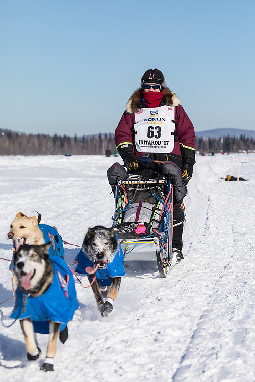 Musher Noah Burmeister competing in the 45rd Iditarod Trail Sled Dog Race on the Chena River after leaving the restart in Fairbanks in Interior Alaska.  Afternoon. Winter.