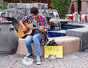 """Please help me get to college"" this guitar player's sign reads.  It says it all. Palm Springs, California"