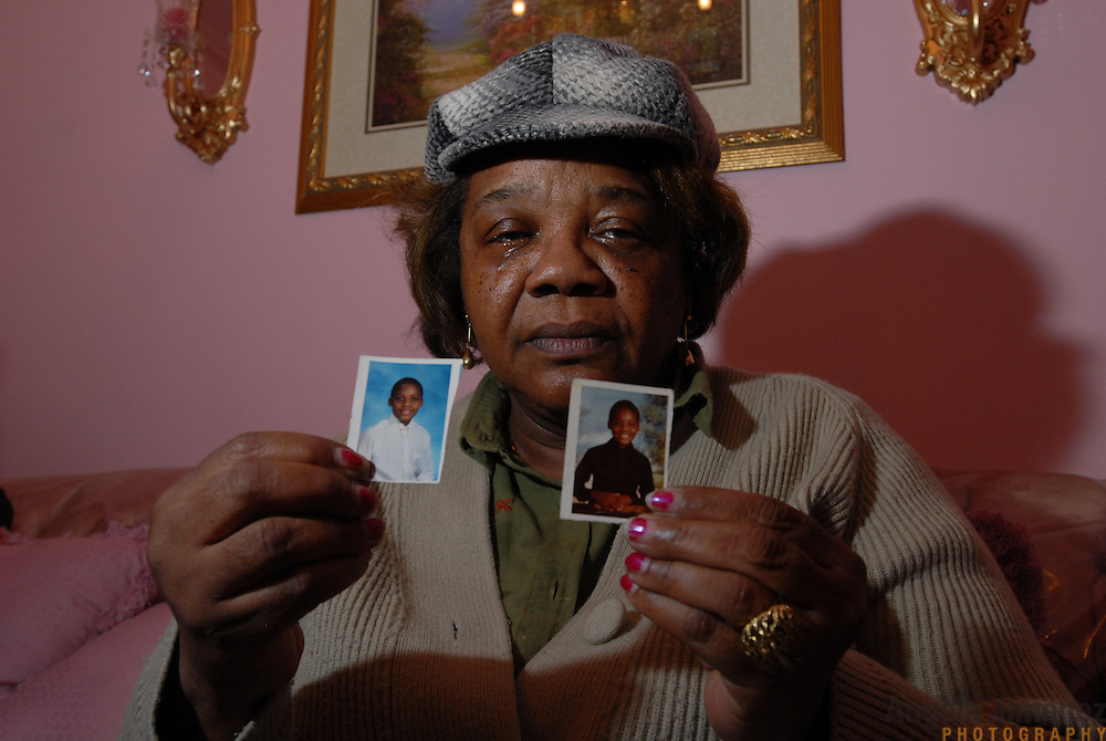 DATE: 11/30/06<br /> DESK: METRO<br /> SLUG: DORISMOND<br /> ASSIGN ID: 30034202A<br /> <br /> Marie Rose Dorismond, whose son, Patrick, 26, was killed by undercover New York City Police narcotics detective Anthony Vasquez during a drug buy-and-bust operation on March 16, 2000 holds the childhood photos she keeps of her son in her wallet in the home of a family member in East Flatbush, Brooklyn after a 27-hour Greyhound bus ride from her home in Port St. Lucie, Florida on November 30, 2006. She has come back to the city to attend the funeral of Sean Bell, 23, who was killed last week by New York City police officers. Vasquez was acquitted of all charges related to the killing of Dorismond's son. <br /> <br /> The photos are of Patrick when he was 7, left, and 5-year-old. <br /> <br /> <br /> photo by Angela Jimenez for The New York Times<br /> photographer contact 917-586-0916