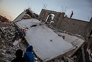 Men working on a destroied house in Khuza'a