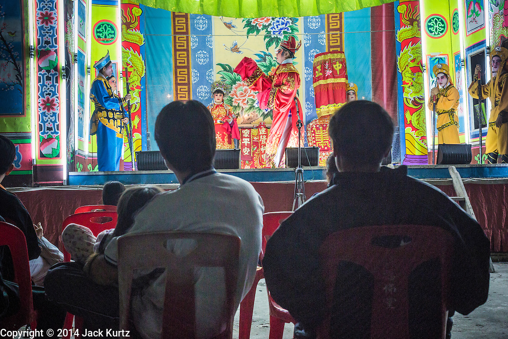 """25 JANUARY 2014 - BANG LUANG, NAKHON PATHOM, THAILAND: The audience watches the Sing Tong Teochew opera troupe during a show in a Chinese shrine in the town of Bang Luang, Nakhon Pathom, Thailand. The Sing Tong Teochew opera troupe has been together for 60 years and travels through central Thailand and Bangkok performing for mostly ethnic Chinese audiences. Chinese opera was once very popular in Thailand, where it is called """"Ngiew."""" It is usually performed in the Teochew language. Millions of Chinese emigrated to Thailand (then Siam) in the 18th and 19th centuries and brought their cultural practices with them. Recently the popularity of ngiew has faded as people turn to performances of opera on DVD or movies. There are still as many 30 Chinese opera troupes left in Bangkok and its environs. They are especially busy during Chinese New Year when travel from Chinese temple to Chinese temple performing on stages they put up in streets near the temple, sometimes sleeping on hammocks they sling under their stage.     PHOTO BY JACK KURTZ"""