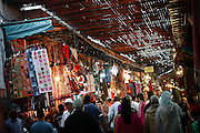 """SHOT 11/1/09 11:29:51 AM - Tourists and locals pass an endless selection of textiles in the Souk Marine in Marrakech or Marrakesh, Morocco. Marrakech is known as the """"Red City"""", is an important and former imperial city in Morocco. It has a population of 1,070,838 (as of 2004), and is the capital of the mid-southwestern economic region of Marrakech-Tensift-Al Haouz, near the foothills of the snow-capped Atlas Mountains. Like many North African and Middle Eastern cities, Marrakech comprises both an old fortified city (the médina) and an adjacent modern city (called Gueliz). Marrakech has the largest traditional market (souk) in Morocco and also has one of the busiest squares in Africa and the world, Djemaa el Fna.[2] The square bustles with acrobats, story-tellers, water sellers, dancers, and musicians. By night, the square turns into food stalls, becoming a huge open-air restaurant. Morocco, officially the Kingdom of Morocco is a country located in North Africa with a population of nearly 32 million people and an area just under 173,000 squrare miles.(Photo by Marc Piscotty / © 2009)"""