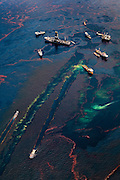 Ships gather near remaining oil platforms near the site of the Deepwater Horizon wellhead, leaving oily wakes as they move through the polluted water, May, 2010.