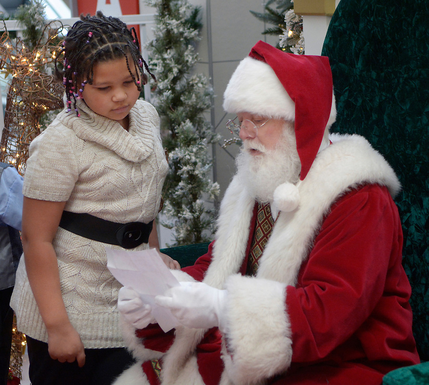 gbs120416f/ASEC -- Tatyana Gabaldon, 9, of Albuquerque, goes over her Christmas list with Santa Claus, aka Dennis Curtis of Rio Rancho, during the Sensitive Santa event at Cottonwood Mall on Sunday morning, Dec. 4, 2016. The RSVP event before regular mall hours provided children with special needs and their families with a sensory friendly environment to safely experience the tradition of visiting Santa Claus. (Greg Sorber/Albuquerque Journal)