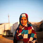 "Malak, 12, arrived from Daraa, Syria in August 2012. Malak has an unusually positive outlook, ""Everything is good. We cope with the sun, we wear hats, sit in the shade. If something happens to us because of the sun, we know to go to the hospital."" Zaatari Camp for Syrian Refugees, Jordan, July 2015."
