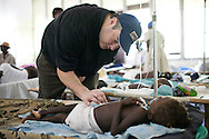 Jason Harris, a pediatric infectious disease specialist volunteering with Project HOPE, examines a young cholera patient at the Hospital Albert Schweitzer on Saturday, October 30, 2010 in Deschapelles, Haiti.