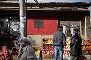 An Albanian Flag painted on the wall above a stall at the city green market in Vushtrri.