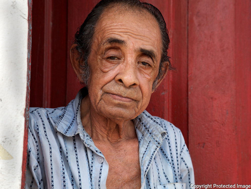 Old man stand in doorway in Flores, Guatemala