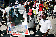 A Haitian man holds up a poster with the face of ousted Presidential Jean-Bertand Aristide at a in a rally in the Cite-Soliel neighborhood of Port-Au-Prince, Haiti February 1, 2006. Demonstrators were protesting the United Nations' plans to have voting stations for voters outside of Cite-Soliel due to security concerns...Photo by Keith Bedford
